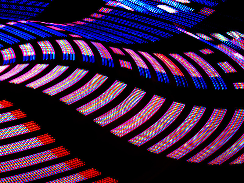 Lights from a spinning ride at a carnival.